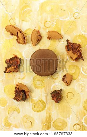 A photo of a chocolate macaron with crumbs, shot from above on a golden yellow background texture, with copy space