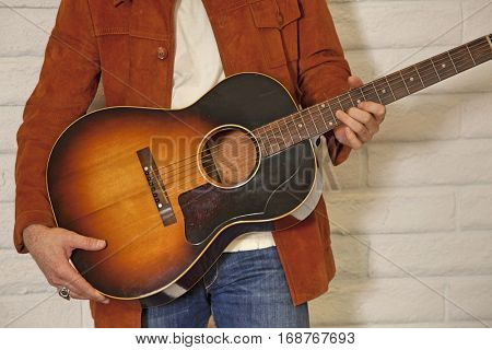Close-up of mid adult man's torso holding guitar