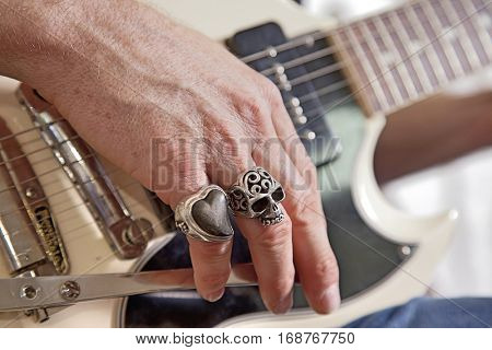 Close-up of mid adult man's fingers with rings playing guitar