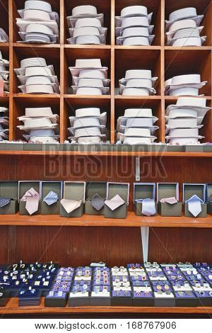 Shirts, neckties and hand cuff links displayed on shelves
