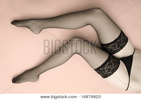 Beautiful slim legs in black nylons on a pink background. Great image for calendar.