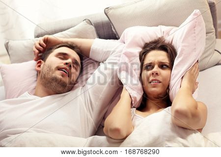 Picture of angry woman in bed with snoring man