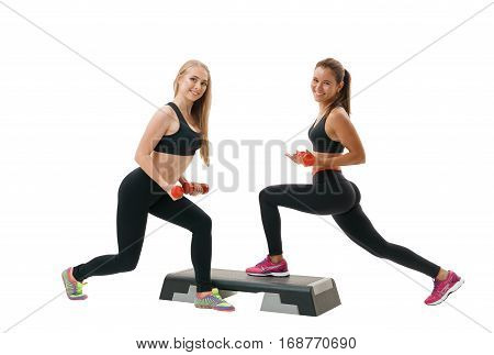Step-aerobics, fitness and shaping concept - two young energetic sporty  women in sportswear exercising with dumbbells and stepper on white isolated background