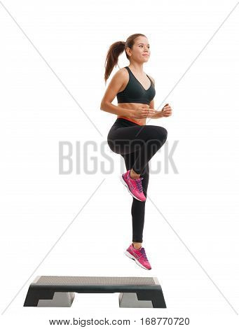 Step-aerobics, fitness and shaping concept - young energetic sporty  woman in sportswear exercising with stepper on white isolated background