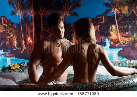 Young sexy couple enjoying jacuzzi at spa hotel during honeymoon vacation