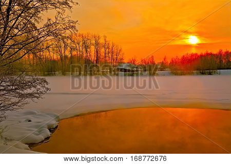 Water and ice on the river trees wooden house on a background of sunset sky