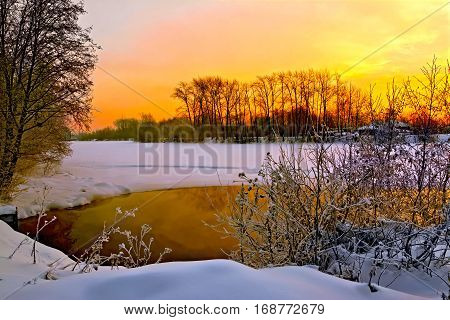 Water and ice on the river shrubs and trees wooden house on a background of sunset sky