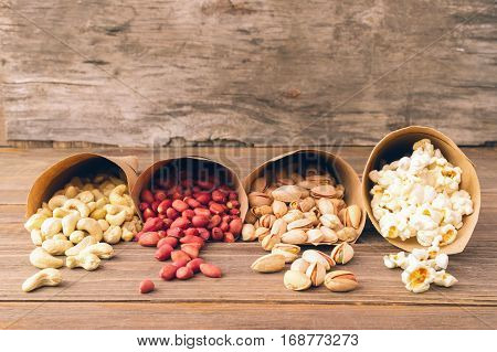Peanuts cashews pistachios popcorn filled paper packets lying the table. Background antique wood. Front view.Horizontal frame