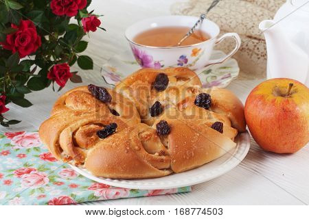 cinnamon raisin bun roll bun with apple and a still life on a plate with bright background