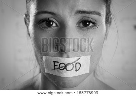 close up face of young beautiful sad latin woman with mouth sealed on stick tape with the text no food and concept of refusing eating and overweight in anorexia bulimia and nutrition disorder concept