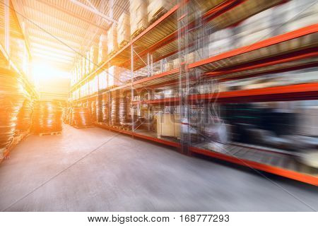 Warehouse industrial and logistics companies. Commercial warehouse. Boxes and crates stocked on the shelves of three storey. The effect of motion blur. Bright sunlight.