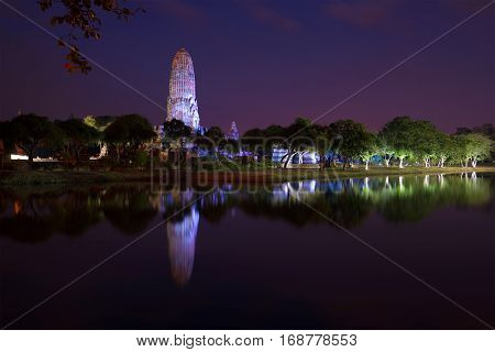 Big prang of an ancient Buddhist temple Wat Phra Ram in the night landscape. Ayutthaya, Thailand
