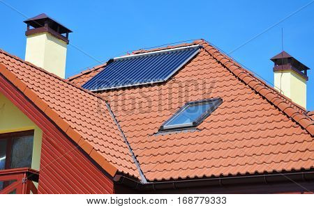 Energy efficiency concept. Closeup of solar water panel heating on red tiled house roof with lightning protection skylights chimney and roof window