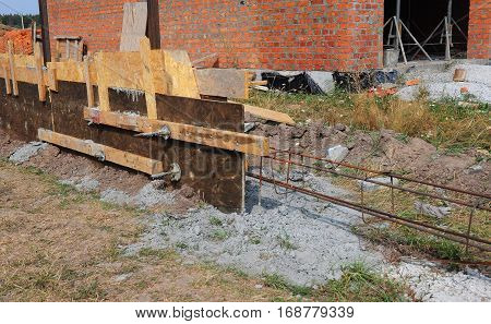 Close up on Building concrete foundation for new fence. Construction site during concrete pouring works with form work.