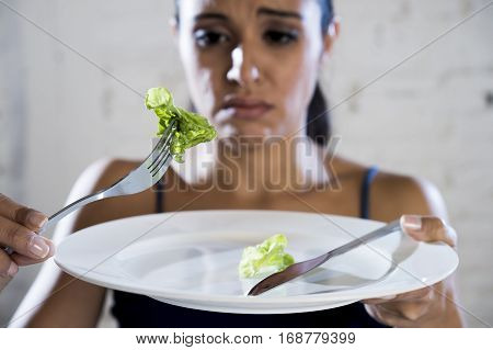 young woman or teen girl holding dish with ridiculous little lettuce as her food symbol of crazy diet in nutrition disorder concept anorexia and bulimia and refusing to eat in diet calories obsession