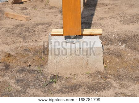 Closeup of wooden pillar on the construction site with screw. Wooden Pillars for terrace.