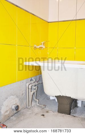 White new bath tube installation water tap in the yellow tiled bathroom. Repair bathroom with new bath tube.