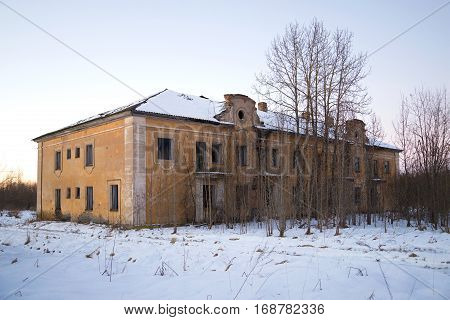 The thrown two-storeyed house in the January evening. The working settlement Russian America of the enterprise for extraction of peat in the Leningrad region. Russia