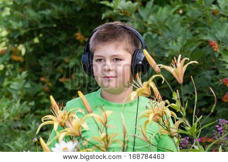 Portrait of a boy with headphones around daylily