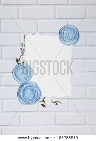 White Background With Handmade Gentle Blue Ranunculus Flowers, Roses and Crystals, Lying Flat on the White Brick Wall, Top View. Have a Empty Rectangular Place For Your Text.