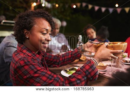 Young black woman passing bowl at a family barbecue