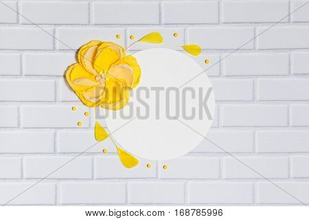 White Background With Handmade Gentle Yellow Flower and Feathers, Lying Flat on the White Brick Wall, Top View. Have an Empty Circle Place For Your Text.