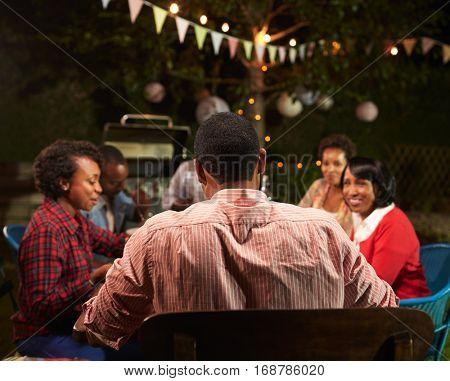 Adult black family enjoying dinner in their garden