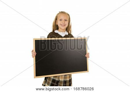 7 or 8 years old little beautiful blond schoolgirl smiling happy and cheerful holding and showing small blank blackboard with copy space in child school education concept isolated on white background