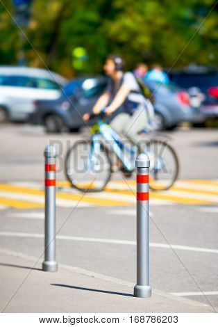 cyclist rides on a pedestrian crossing in the foreground metal bollards