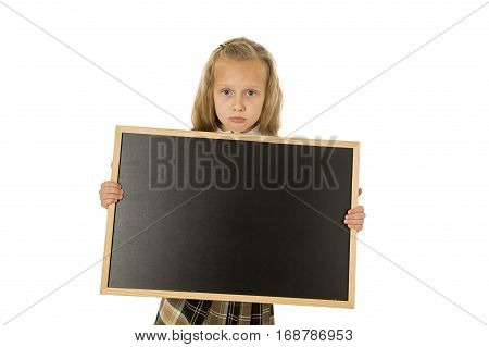 7 or 8 years old little beautiful blond schoolgirl sad moody and tired holding and showing small blank blackboard with copy space in child school education concept isolated on white background