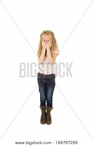 sweet young 7 or 7 years old little schoolgirl with blond hair in jeans and casual shirt covering her face with her hands crying sad victim of bullying at school isolated on white background