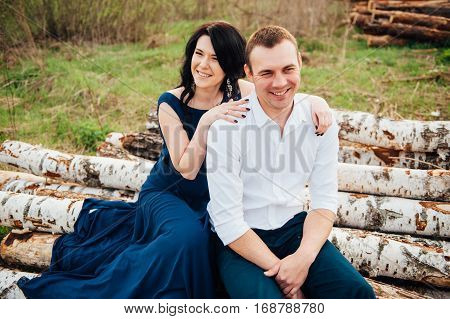 Happy Couple In Love Sitting On A Log And Laughing