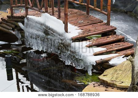 Icicles hanging from a bridge over a frozen lake.