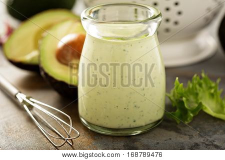 Homemade avocado ranch dressing in a small jar with fresh greens