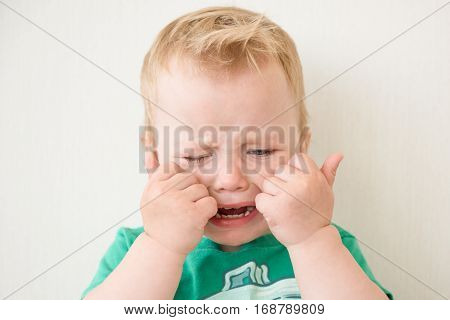 Crying little boy closing face with hands