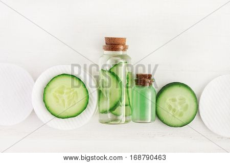 Cucumber refreshing diy facial tonic in bottle, fresh green slices, white wooden surface.