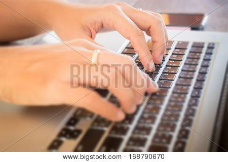 Typing on keyboard laptop at work table stock photo