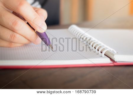Woman hand writing on noteboook paper stock photo