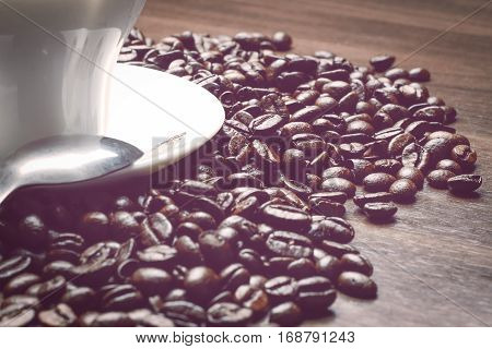 Coup of coffe alongside with coffe beans on wooden table alongside with spoon