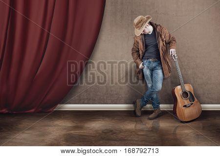 The cowboy with guitar near a curtain.
