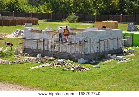 Building house from aerated concrete building blocks. Builders laying blocks.
