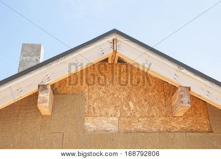 Attic insulation. New house wall facade insulation against blue sky. Roof insulation detail. Building insulation added to buildings for comfort energy saving and energy efficiency. Attic Construction.