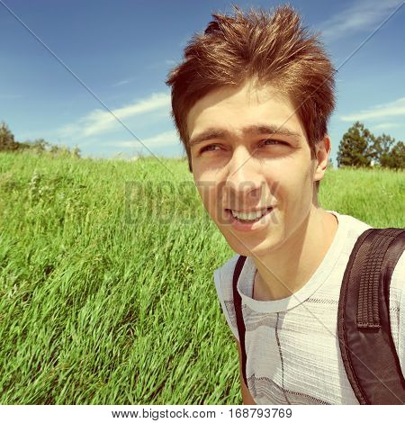 Toned Photo of Teenager with Knapsack walk in the Summer Field