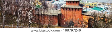 Kremlin wall in Nizhny Novgorod Russia in spring with river and modern city at the background. Trees and cloudy sky in Nizhny Novgorod Russia