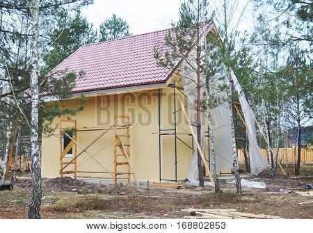 Construction or repair of the rural house with balcony eaves windows chimney roofing fixing facade insulation plastering and using color. House construction.