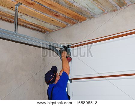 KYIV, UKRAINE - March 1, 2017:  Contractor Installing Garage Door Post Rail and Spring Installation and Garage Ceiling. Spring Tension Lifts Metal Section Garage Door Panel that the Motor does not have to Lift Entire Weight.