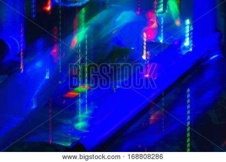 Abstract background of motion blurred neon lights under ultraviolet lamp.