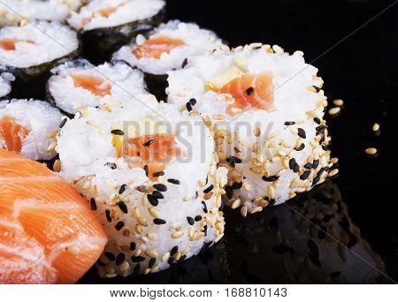 Sushi pieces over black reflecting plate horizontal image