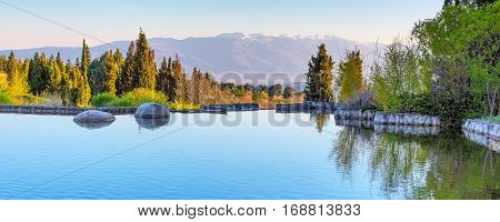 Panoramic lake and mountains landscape view with trees and snow mountains peaks on the background in Sandanski, Bulgaria