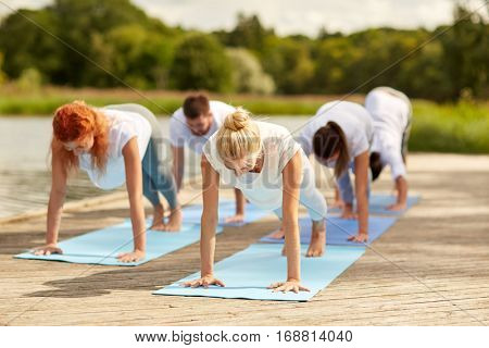fitness, sport, yoga and healthy lifestyle concept - group of people making plank exercise on river or lake berth